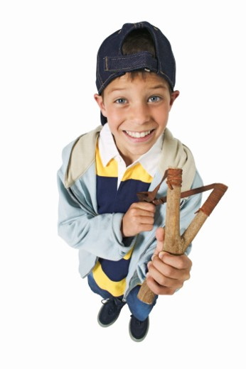 elevated view of a boy (11-12) holding a slingshot : Stock Photo