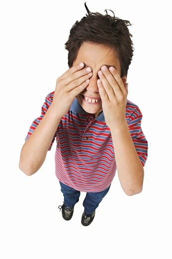 Elevated view of a boy (11-12) covering his eyes : Stock Photo