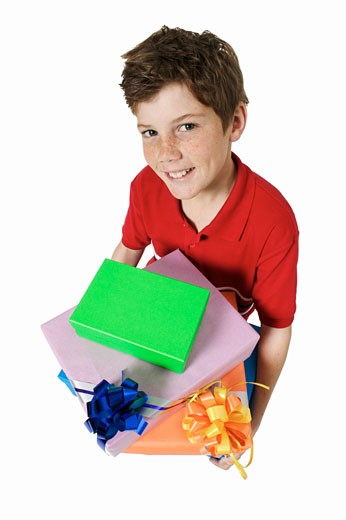 Elevated view of a smiling boy (12-13) holding presents : Stock Photo