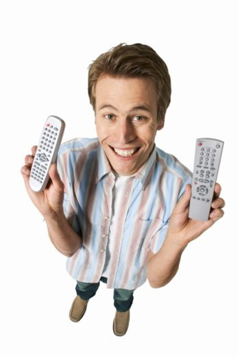Stock Photo: 1491R-1066080 Man holding two remote controls