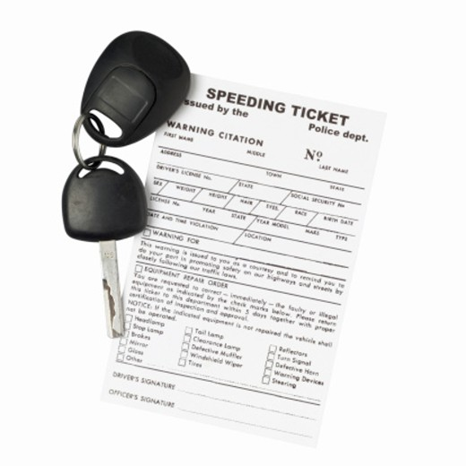 Close up view of a speeding ticket and a car key : Stock Photo