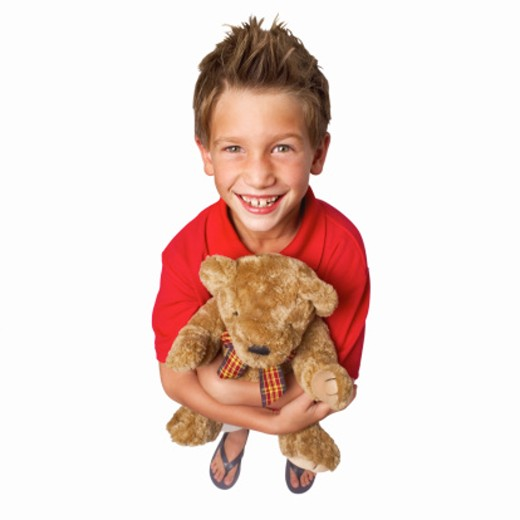 Elevated view of a boy (10-11) holding a teddy bear : Stock Photo