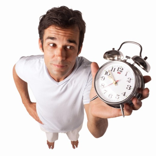 Elevated view of a man holding an alarm clock : Stock Photo
