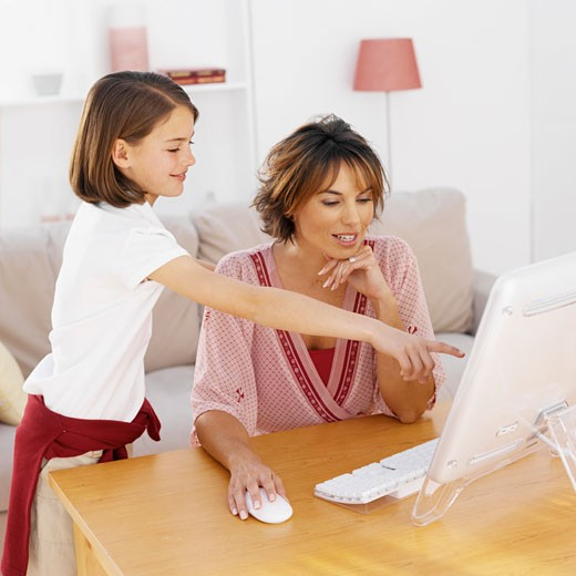 Mother using a computer with her daughter (9-10) : Stock Photo