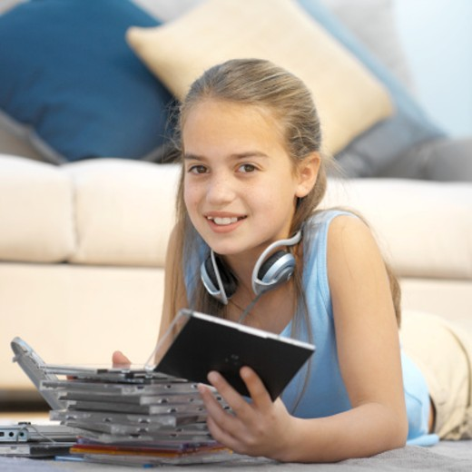 Stock Photo: 1491R-1069324 Close-up of girl (11-12) looking through collection of cds with headphones around neck