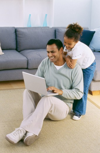 Close-up of father working on laptop with daughter watching him (8-9) : Stock Photo