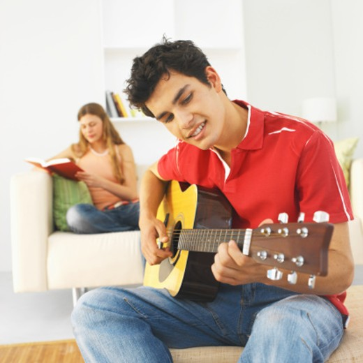 Stock Photo: 1491R-1069432 Young man playing guitar and young woman reading a book