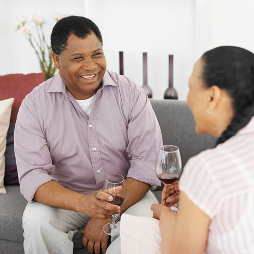 Mature couple sitting on sofa and holding glasses of wine : Stock Photo