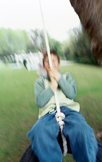 Close-up of boy (10-11) playing on tire swing : Stock Photo