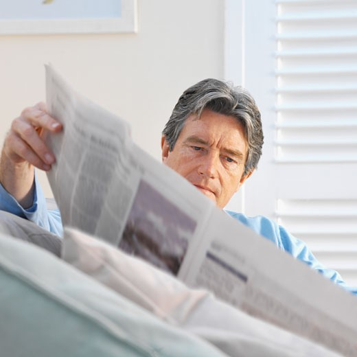 Stock Photo: 1491R-1069574 Close-up of a mature man sitting on sofa reading newspaper