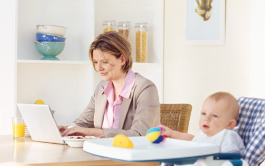 Side view of mother having breakfast with baby girl sitting in high chair (6-12 months) : Stock Photo