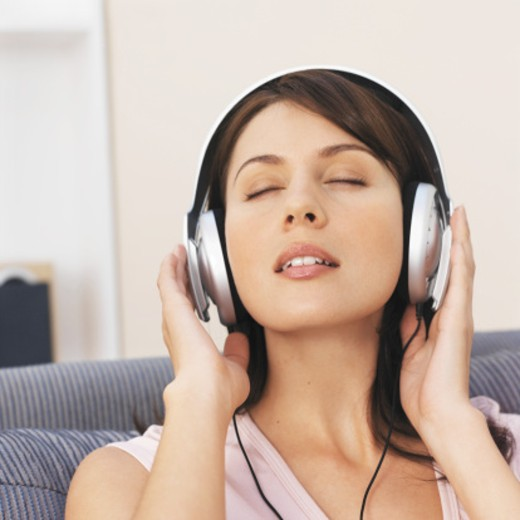 Stock Photo: 1491R-1069733 Close-up of young woman listening to music with headphones