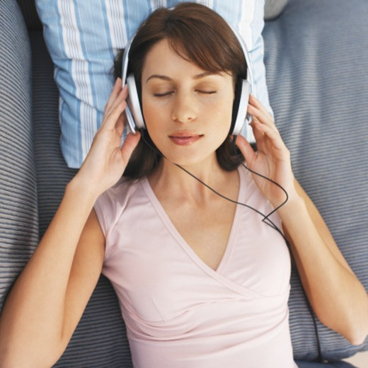 Close-up of young woman listening to music with headphones : Stock Photo