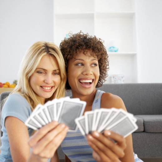 Front view of two young women playing cards : Stock Photo