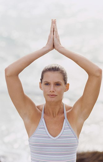 Close-up of a young woman at the beach practicing the tree yoga position : Stock Photo