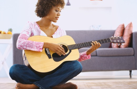 Stock Photo: 1491R-1069915 Portrait of a young woman playing an acoustic guitar