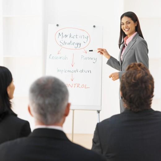 Businesswoman giving presentation to three business executives : Stock Photo