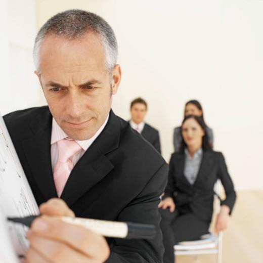 Stock Photo: 1491R-1070038 Businessman giving presentation to three business executives