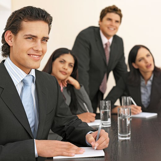 Close-up of four business executives having a meeting in boardroom : Stock Photo