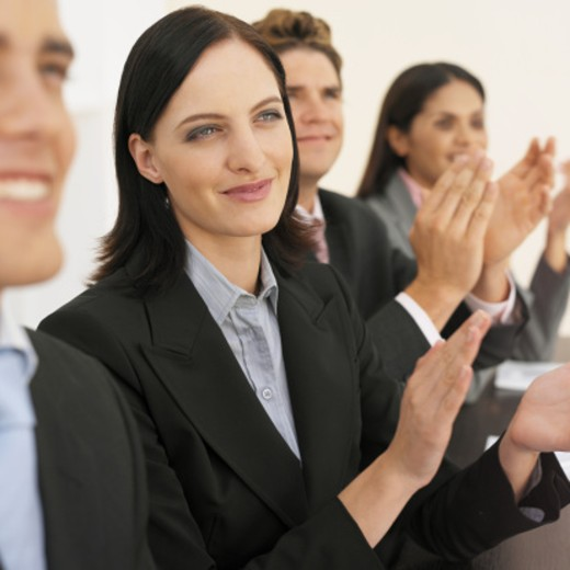 Close-up of four business executives applauding : Stock Photo