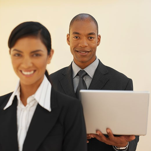 Stock Photo: 1491R-1070114 Front view of a businesswoman and a businessman holding a laptop