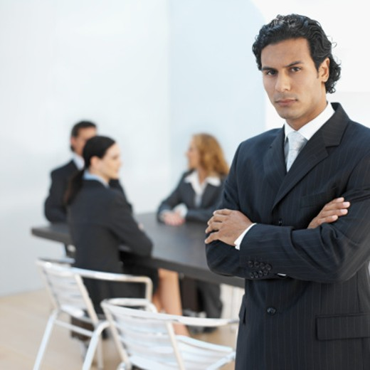 Three business executives sitting in boardroom with fourth executive standing with arms folded : Stock Photo