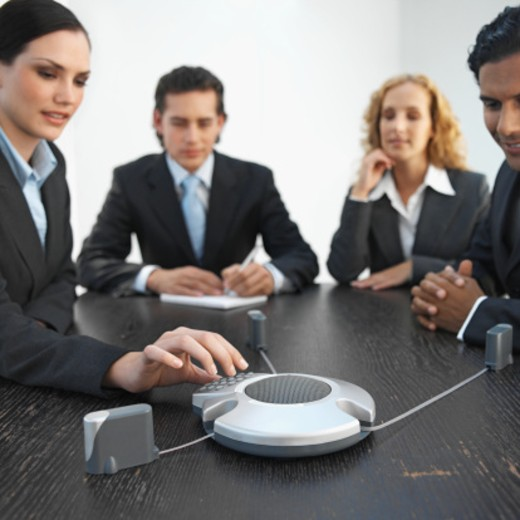 Four business executives having conference call in a boardroom : Stock Photo