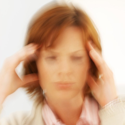 Close-up of young woman with hand touching her head (blurred) : Stock Photo