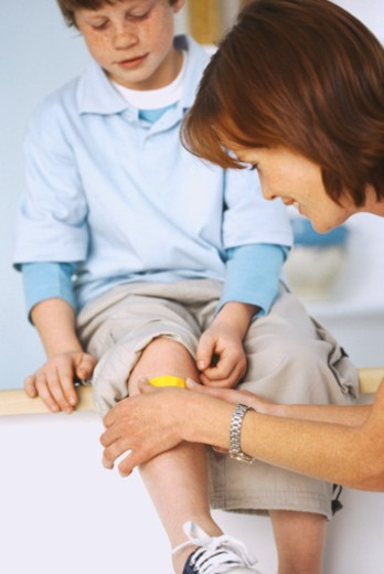 Stock Photo: 1491R-1070524 Close-up of a woman applying a bandage to a boy's (8-10) knee