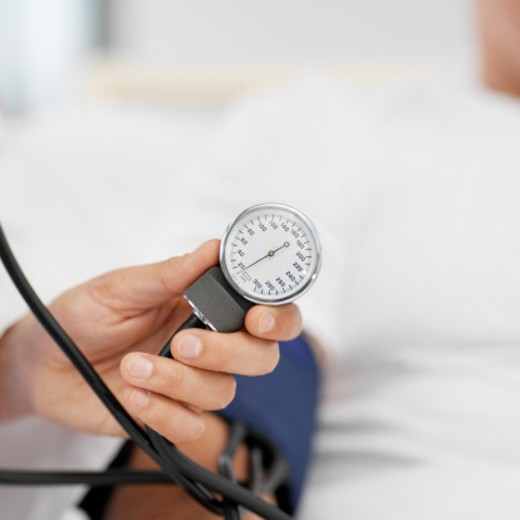 Close-up of doctor taking blood pressure of patient : Stock Photo