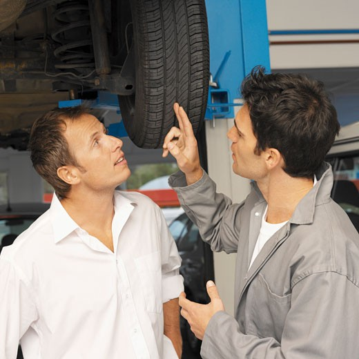 Close-up of mechanic showing customer problem with car wheel : Stock Photo
