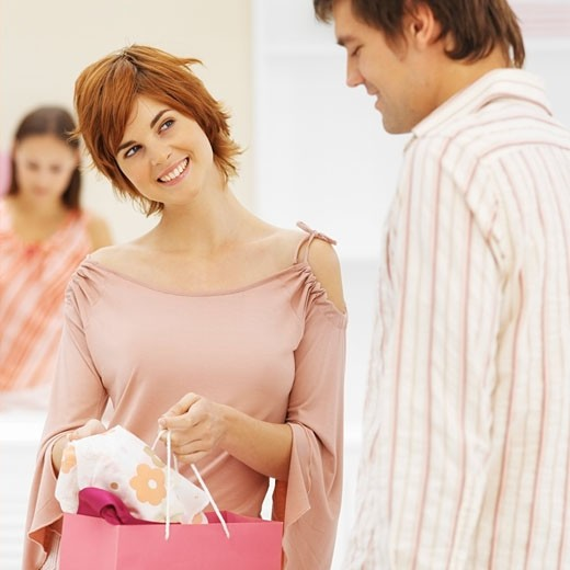 Young woman showing young man item of clothing from shopping bag : Stock Photo