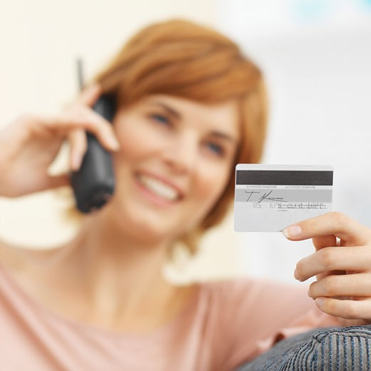Stock Photo: 1491R-1070942 Close-up of young woman talking on mobile phone and holding credit card