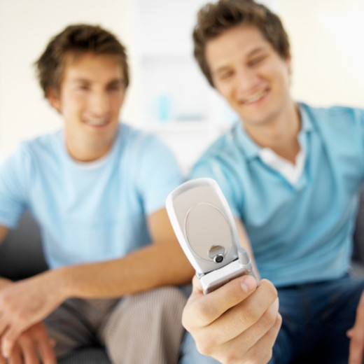 Close-up of two young men sitting on sofa and looking at mobile phone : Stock Photo