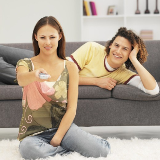Front view of young man lying on sofa with young woman holding remote control : Stock Photo