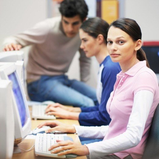 Close-up of three young people sitting in computer lab : Stock Photo