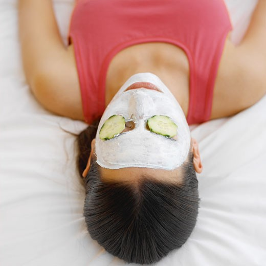 Stock Photo: 1491R-1071232 Woman wearing a face mask with cucumber on her eyes