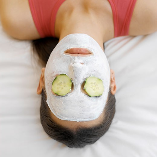 Woman wearing a face mask with cucumber on her eyes : Stock Photo