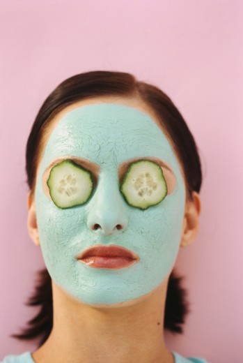 woman lying down with a face pack and cucumber slices : Stock Photo