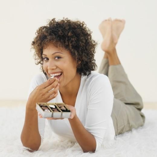 Woman enjoying a box of chocolates : Stock Photo