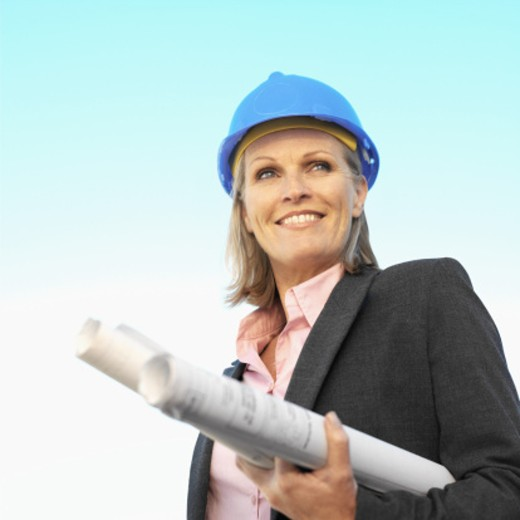 Close-up businesswoman wearing hard hat and holding blueprint under her arm : Stock Photo