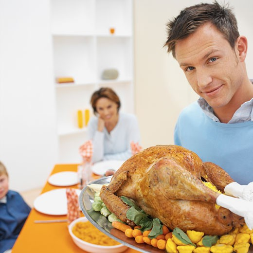 Father holding a plate of roast chicken and vegetables with her family in the background : Stock Photo