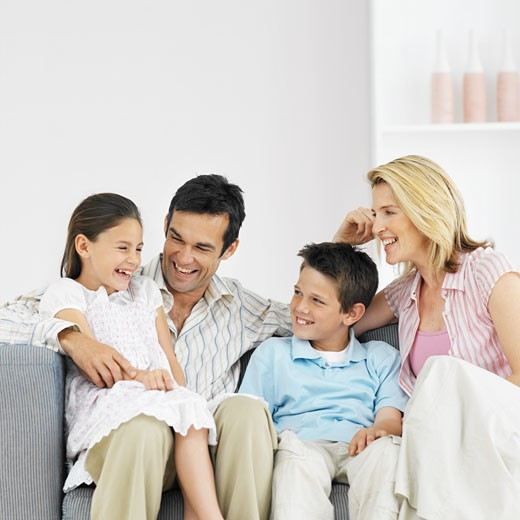 Close-up of parents and two children sitting on sofa (10-12) : Stock Photo