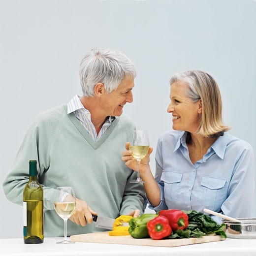 Stock Photo: 1491R-1071758 Side view of mature man cutting bell peppers and mature woman holding glass of wine