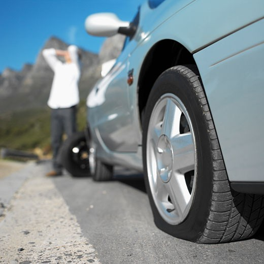 Close-up of car with flat tire and young man with hands on his head : Stock Photo