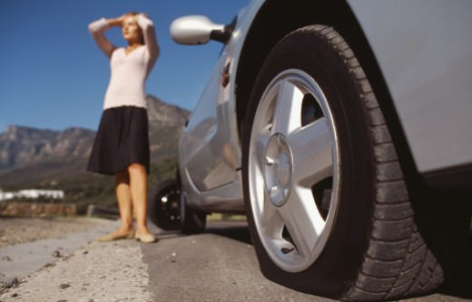 Close-up of car with flat tire and young woman with hands on his head : Stock Photo
