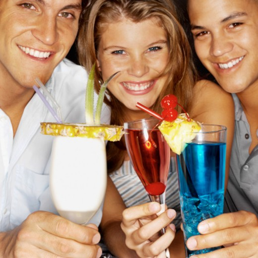 Front view portrait of three young people holding cocktails : Stock Photo