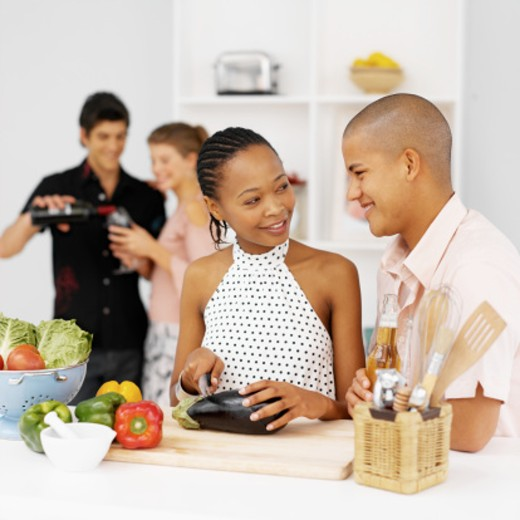 Two young people preparing food and two other people in background drinking wine : Stock Photo