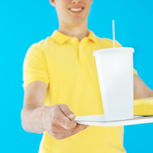 Close-up of young waiter holding fast food tray : Stock Photo