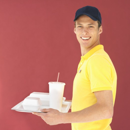 Stock Photo: 1491R-1072113 Close-up of young waiter holding fast food tray